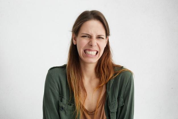 Ujęcie w głowę pięknej kobiety w swobodnym ubraniu z niechęcią, patrzącej z niezadowolonym wyrazem twarzy, demonstrującym jej obrzydzenie.