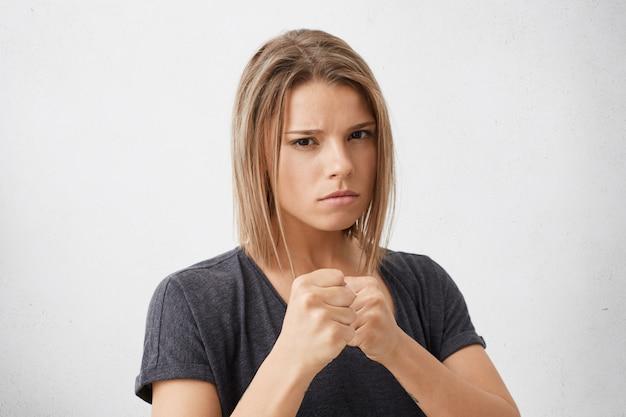 Ujęcie w głowę pięknej młodej kobiety rasy mieszanej, trzymającej przed sobą zaciśnięte pięści, gotowej do walki, broniącej siebie i swoich przekonań, z gniewnym spojrzeniem. agresja, konflikt i przemoc
