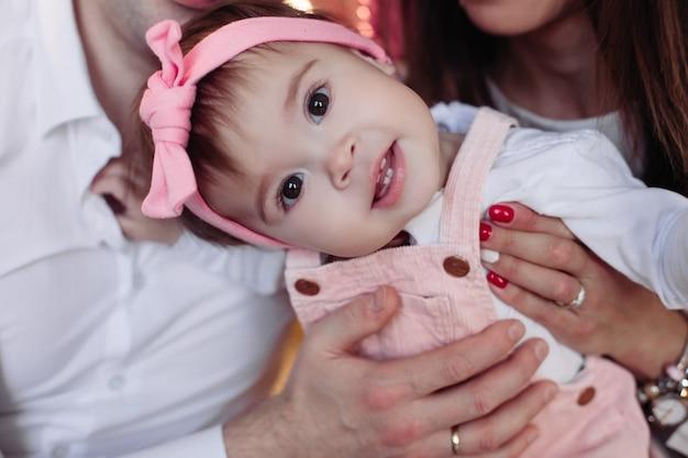 Ujęcie w głowę ślicznej dziewczynki w różowej opasce z kokardką, ciekawie patrzącej z przodu