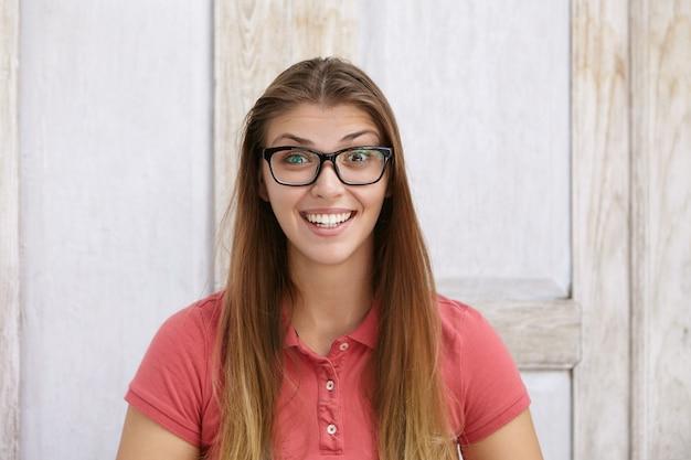 Ujęcie w głowę szczęśliwej i podekscytowanej młodej kobiety w prostokątnych okularach przeciwsłonecznych, która patrzy, unosząc brwi ze zdumienia
