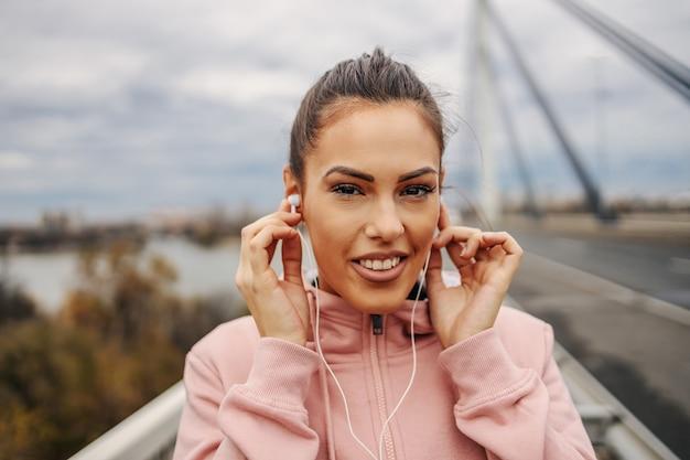 Ujęcie w głowę uroczej uśmiechniętej młodej sportsmenki stojącej na moście, zakładającej słuchawki, przygotowującej się do biegania.