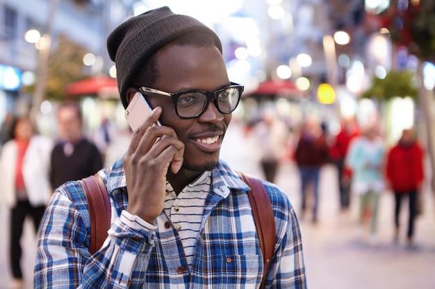 Ujęcie w głowę wesołego, nowoczesnego młodego afrykańskiego turysty z plecakiem w kapeluszu i okularach, prowadzącego rozmowę telefoniczną podczas spaceru po zatłoczonej ulicy podczas letnich wakacji w obcym kraju