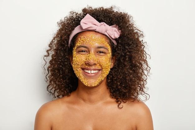 Ujęcie w głowę wesołej afroamerykanki nakłada na twarz naturalną maskę peelingującą, dodaje blasku i peelinguje martwy naskórek, zabija różne bakterie, nosi pałąk, ma kędzierzawe włosy, nagie ramiona. pojęcie piękna