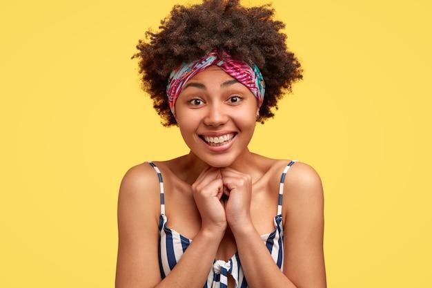 Ujęcie w głowę zadowolonej, dotkniętej młodej afroameryki, uśmiechającej się delikatnie, czuje się zadowolona, nosi top w paski i nakrycie głowy