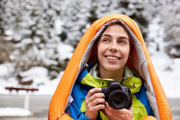 Ujęcie w głowę zadowolonej podróżniczki, która odpoczywa w zaśnieżonych górach, robi zdjęcia widokowego widoku, pozuje w zimowej przestrzeni, uśmiecha się delikatnie