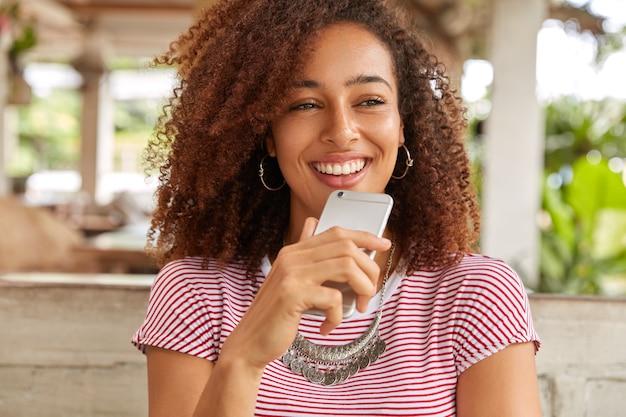 Ujęcie w głowę zadowolonej uroczej kobiety z fryzurą afro, skupiona w oddali, czeka na telefon komórkowy, spędza wolny czas w kawiarni, ubrana niedbale, siedzi w kafeterii na tarasie