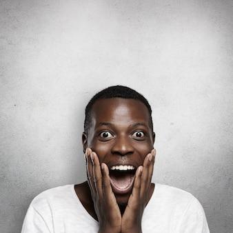 Ujęcie w głowę zaskoczonego, radosnego studenta z afryki ze zdumieniem, trzymającego dłonie na policzkach, szeroko otwierającego usta, zszokowanego niespodziewanym sukcesem na egzaminach na uniwersytecie