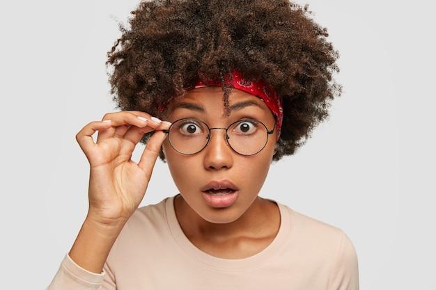 Ujęcie w głowę zszokowanej wzruszającej młodej kobiety z krzaczastą fryzurą w stylu afro