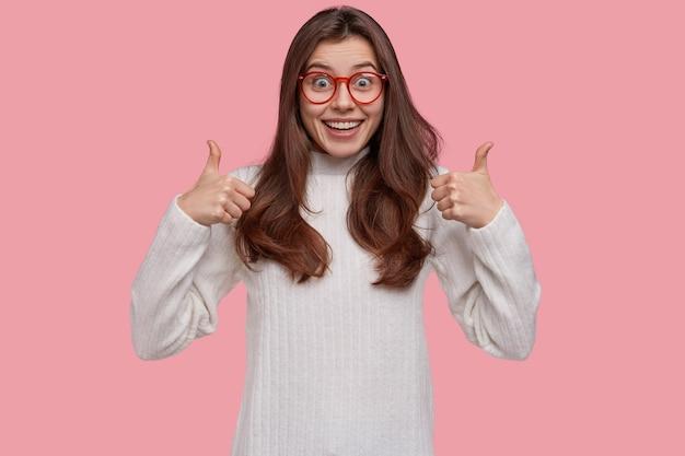 Ujęcie w górę atrakcyjnej pani akceptuje plan znajomych, daje pozytywną opinię, trzyma kciuki do góry, patrzy szczęśliwie w kamerę