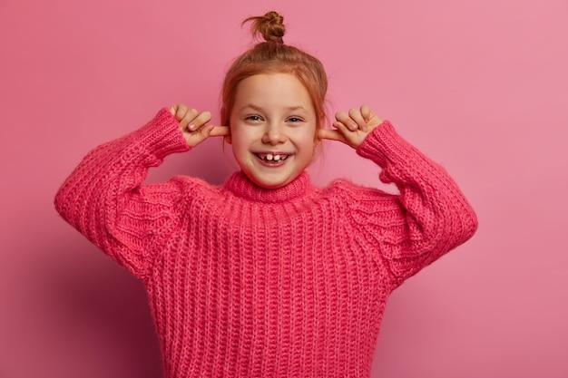 Ujęcie w górę całkiem radosnej małej dziewczynki zatykającej uszy palcami wskazującymi, radośnie się śmieje, ignoruje głośny dźwięk, ma kok do włosów, nosi dzianinowy sweter, pozuje na różowej ścianie. nie słyszę cię