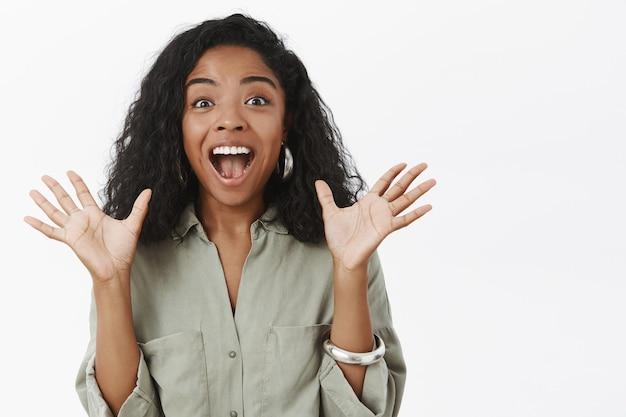 Ujęcie w górę entuzjastycznej czarującej kobiety o ciemnej karnacji z kręconymi, stylowymi fryzurami, unoszącej dłonie w podnieceniu