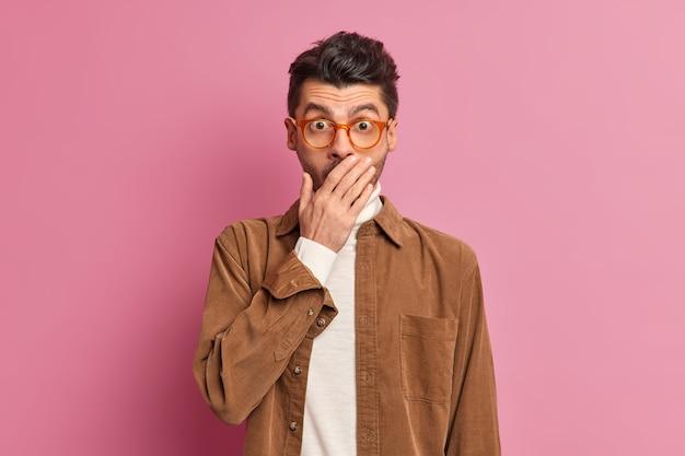 Ujęcie w górę imponującego nieogolonego faceta zakrywającego usta, wpatrującego się w aparat, jest bardzo zdziwione