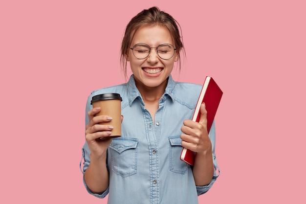 Ujęcie w górę ładnej uśmiechniętej kobiety czerpie przyjemność z nauki