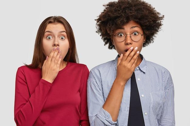 Ujęcie w górę oszołomionych, emocjonalnych kobiet z dwóch mieszanych ras patrzy ze zdumieniem