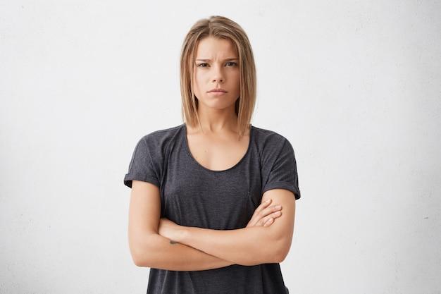 Ujęcie w górę pięknej, zirytowanej młodej kobiety ze strzyżoną fryzurą, trzymającej ręce skrzyżowane, o sceptycznej, wściekłej twarzy i całym wyrazie zazdrości lub podejrzliwości.