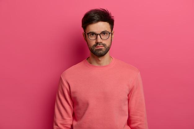 Ujęcie w górę poważnego męskiego menedżera lub freelancera wygląda ze spokojnym wyrazem twarzy, gdzieś skupiony, przychodzi na rozmowę kwalifikacyjną, nosi przezroczyste okulary i sweter, pozuje na różowej ścianie