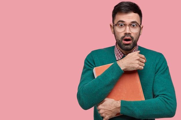 Ujęcie w górę przystojnego, przerażonego młodego mężczyzny ma oszołomiony wyraz twarzy, trzyma stary podręcznik, ma atrakcyjny wygląd, nosi okulary
