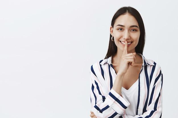 Ujęcie w górę przystojnej pięknej kobiety w bluzce w paski na koszulce, szeroko uśmiechającej się, mówiącej ciii, wykonującej gest uciszenia z palcem wskazującym na ustach, zdradzającej sekret przyjacielowi