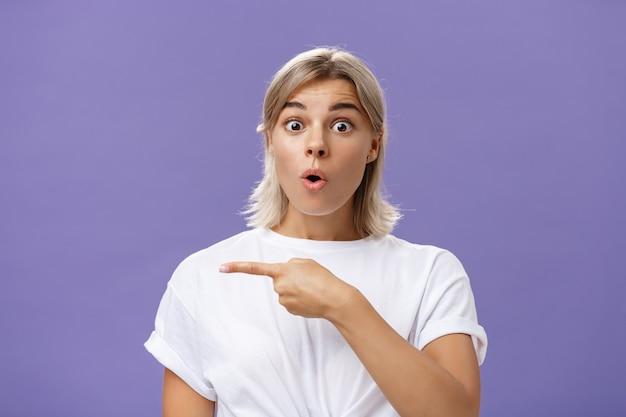 Ujęcie w górę przytłoczonej, podekscytowanej i zaskoczonej atrakcyjnej miejskiej kobiety w białej koszulce ze złożonymi ustami, sapiącymi ze zdumienia, zadając pytanie i wskazując w lewo na fioletową ścianę