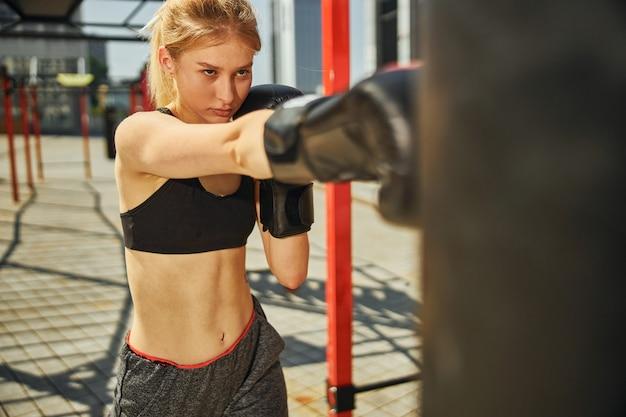 Ujęcie w górę sportowej kobiety, która boksuje prawą ręką i patrzy na worek treningowy na boisku sportowym