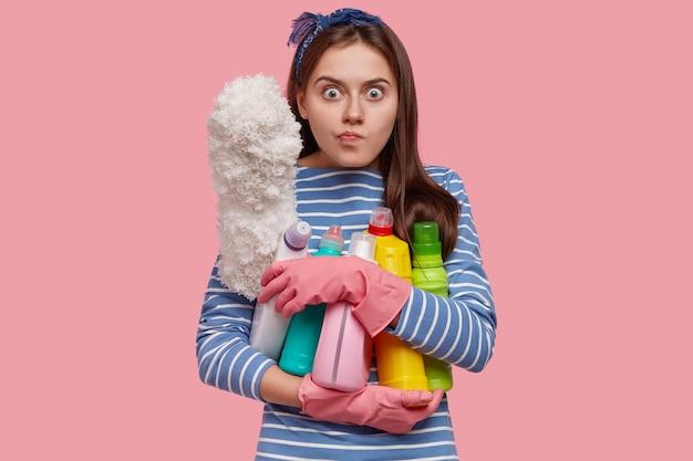 Ujęcie w górę wściekłej gospodyni domowej, która trzyma blisko butelki z płynnym detergentem i szczotkuje, zajęta pracami domowymi, nosi sweter w paski