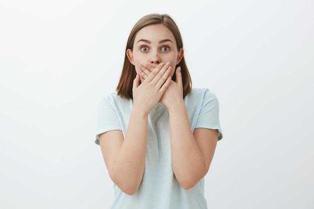 Ujęcie w górę zdumionej, oszołomionej kobiety uczącej się szokującej plotki zakrywającej usta z obiema dłońmi wpatrującymi się w zdumienie, będąc pod wrażeniem i podekscytowanym, pozując na szarej ścianie