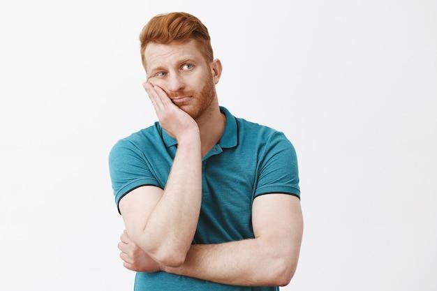 Ujęcie w górę znudzonego i zmęczonego, ponurego rudowłosego faceta z włosiem w zielonej koszulce polo, opierającego twarz na dłoni, wpatrującego się w prawo z wyczerpanym i nieostrożnym wyrazem twarzy, nie mającego nic do roboty na szarej ścianie
