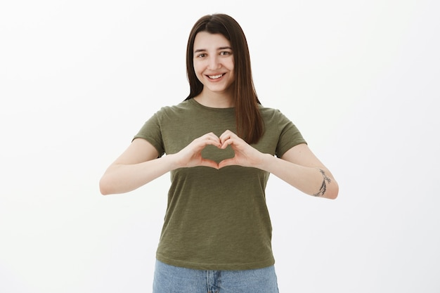 Ujęcie w pasie miłej i szczerej atrakcyjnej młodej brunetki z tatuażem, pokazującym serce na ciele i uśmiechniętą uroczą, wyznającą miłość, wykonującą romantyczny gest i dzielącą się miłością