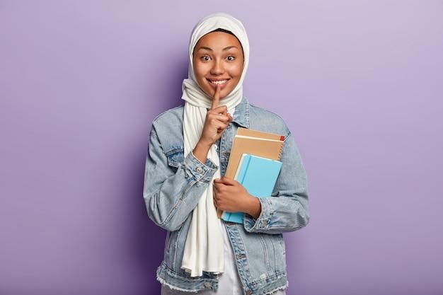 Ujęcie w pasie szczęśliwej muzułmańskiej kobiety z radosnym wyrazem twarzy, wykonuje gest uciszenia, pokazuje białe zęby, trzyma spiralny notatnik, nosi biały szalik, dżinsową kurtkę, odizolowaną na fioletowej ścianie
