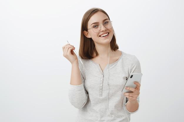 Ujęcie w pasie wesołej uroczej kobiety rasy kaukaskiej w modnych okularach trzymającej smartfon zdejmującej słuchawki i wpatrującej się beztrosko w słuchanie ulubionej piosenki przerywającej rozmowę z przyjacielem