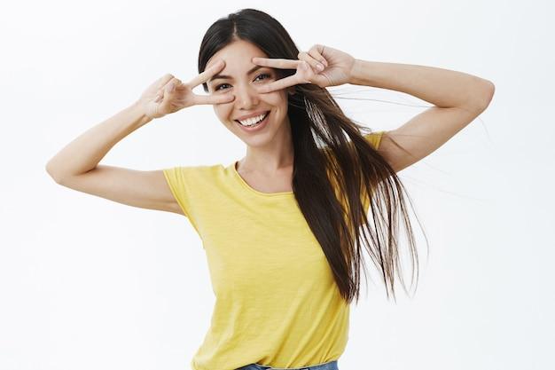 Ujęcie w pasie zadowolonej beztroskiej modelki w żółtej casualowej koszulce przedstawiającej gest pokoju lub dyskoteki