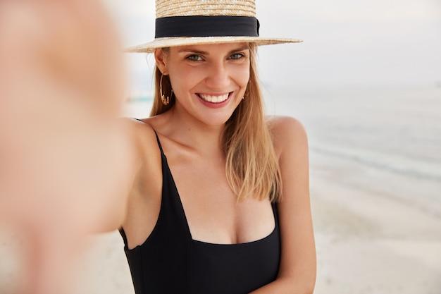 Ujęcie w plenerze uroczej modelki w kostiumie kąpielowym i czapce, wyciągającej rękę, by zrobić sobie selfie lub zdjęcie, zachwycona wyglądem, który odpoczywa na wybrzeżu, cieszy się dobrym odpoczynkiem i letnią pogodą