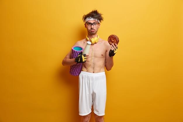Ujęcie w pomieszczeniach niezadowolonego sportowca, który czuje pokusę zjedzenia fast foodów, nosi wałek z pianki, chce mieć idealne ciało, nosi słuchawki stereo na szyi, szorty, opaskę na głowę, rękawiczki sportowe, ćwiczy