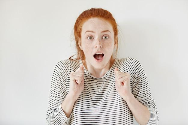 Ujęcie w pomieszczeniach szczęśliwej ekstatycznej młodej kobiety z piegami, która ma zszokowany wygląd, wykrzykuje, trzyma szeroko otwarte usta i zaciśnięte pięści, świętując sukces, zaskoczona jej nieoczekiwanym zwycięstwem