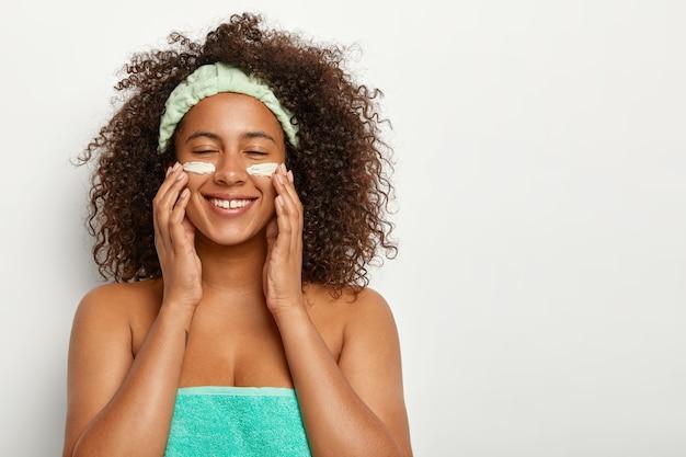 Ujęcie w pomieszczeniach zadowolonej kobiety z afro hairstye, nakłada krem kosmetyczny do pielęgnacji skóry, uśmiecha się pozytywnie, ma świeżą, czystą twarz, używa kremu nawilżającego na dzień lub balsamu przeciwdziałającego efektom starzenia, owinięty turkusowym ręcznikiem
