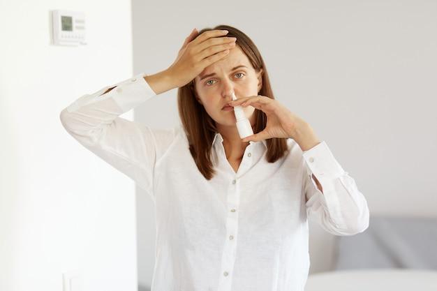 Ujęcie w pomieszczeniu chorej kobiety w białej koszuli w stylu casual, stojącej z ręką na czole i używającej sprayu do nosa, czuje grypę i katar, ma wysoką temperaturę.