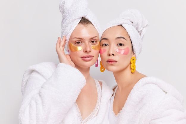 Ujęcie w pomieszczeniu dwóch różnych kobiet stojących blisko siebie nakładając kolagenowe plastry pod oczy