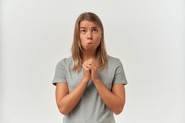 Ujęcie w pomieszczeniu młodej dorosłej kobiety, nosi szarą koszulkę, patrzy w górę, trzyma dłonie razem w pozycji do modlitwy i gryzie usta na biało