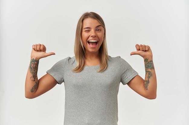 Ujęcie w pomieszczeniu młodej dorosłej kobiety, szeroko uśmiechniętej, pokazującej idealne zęby, wskazującej dwoma kciukami na siebie,