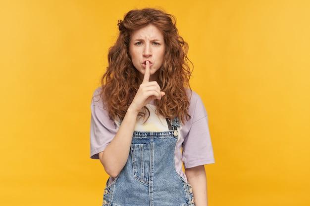 Ujęcie w pomieszczeniu młodej negatywnej, zmęczonej kobiety, z rudymi, falującymi długimi włosami, pokazuje gest ciszy z szalonym i nerwowym wyrazem twarzy. na białym tle nad żółtą ścianą