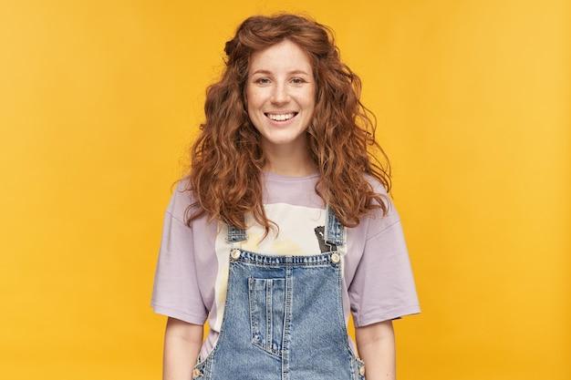 Ujęcie w pomieszczeniu młodej pozytywnej kobiety, nosi niebieskie dżinsowe kombinezony i fioletową koszulkę, czuje się szczęśliwa i zadowolona, patrzy z przodu z pozytywnym wyrazem twarzy