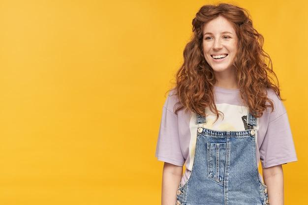 Ujęcie w pomieszczeniu młodej pozytywnej kobiety, nosi niebieskie dżinsowe kombinezony i fioletową koszulkę, czuje się szczęśliwa i zadowolona, wygląda na bok z pozytywnym wyrazem twarzy