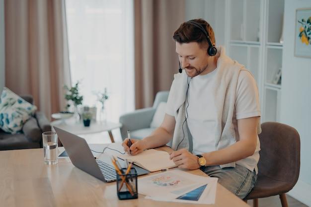 Ujęcie w pomieszczeniu szczęśliwego mężczyzny robi notatki podczas słuchania kursów online, studiuje zdalnie z domu, siedzi przy biurku z papierami na nowoczesnym laptopie, nosi słuchawki, prowadzi konferencję internetową lub wirtualne spotkanie