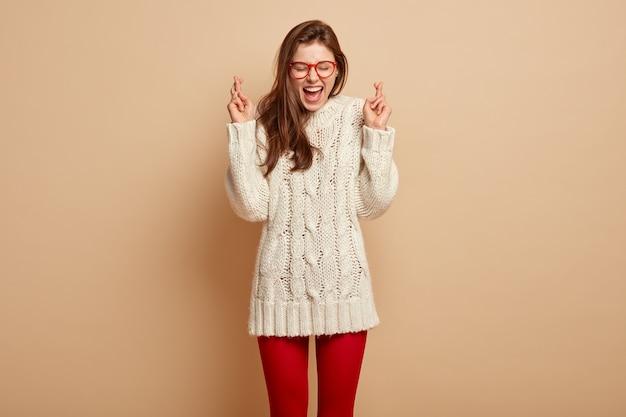 Ujęcie w pomieszczeniu wesołej, radosnej młodej kobiety krzyżuje palce, ma nadzieję, że wszystko będzie dobrze, nosi biały sweter, czerwone legginsy, ma ochotę na spełnienie marzeń, stoi na beżowej ścianie