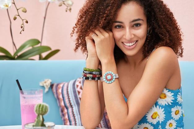 Ujęcie w pomieszczeniu zadowolonej młodej pięknej kobiety z fryzurą afro, ubrana w letnie ubrania, pozuje na niebieskiej sofie z koktajlem w przytulnej kawiarni z orchideą