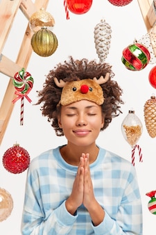 Ujęcie w pomieszczeniu zadowolonej, szczęśliwej młodej kobiety trzymającej dłonie w geście modlitwy, życzy sobie w wigilię nowego roku, zamyka oczy i uśmiecha się delikatnie wstaje