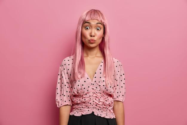 Ujęcie w pomieszczeniu zaskoczonej kobiety wydyma usta i unosi brwi, czuje się zszokowana, patrząc na swoją nową fryzurę, ufarbowane na różowo włosy