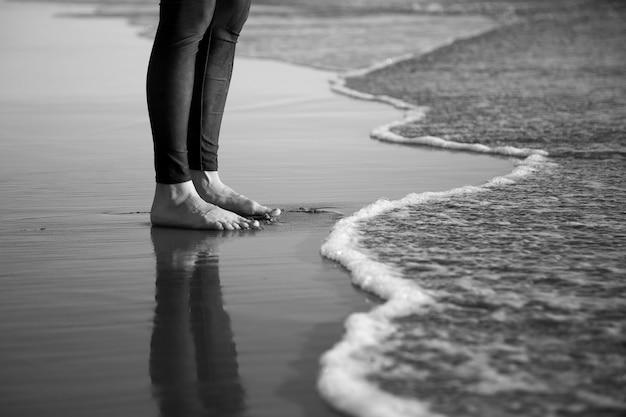 Ujęcie w skali szarości bosych nóg człowieka stojącego na piaszczystej plaży