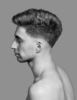 Ujęcie w skali szarości młodego mężczyzny na szarym tle