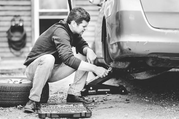 Ujęcie w skali szarości przedstawiające mężczyznę naprawiającego koło